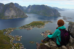 Girl on a cliff. Girl sitting on a cliff and looking at the Reine Stock Photo