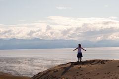 Girl on Cliff with Arms Spread Royalty Free Stock Photography