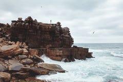 Girl on cliff near sea Stock Photos