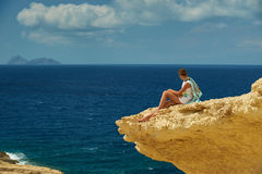A girl on the cliff. A girl is sitting on the clif and observing the sea Stock Photos
