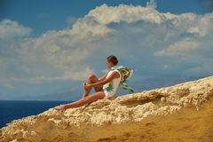 A girl on the cliff. A girl is sitting on the clif and observing the sea Royalty Free Stock Photography