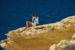 A girl on the cliff. A girl is sitting on the clif and observing the sea Stock Images