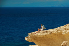 A girl on the cliff. A girl is sitting on the clif and observing the sea Royalty Free Stock Images