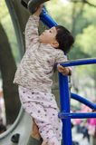 Girl climb ladder. Baby climb the sports equipment in park Royalty Free Stock Photography