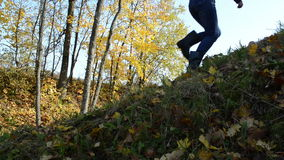 Girl climb walk hill autumn color sunlighted trees move wind stock footage