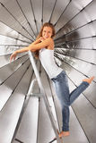 Girl climbed on ladder near silver umbrella Royalty Free Stock Images