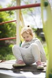 The little girl climbed onto a children slide on a playground for children and is very happy to play royalty free stock photos