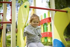 The little girl climbed onto a children slide on a playground for children and is very happy to play stock photo