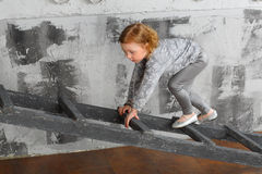 A girl climbed up the ladder Royalty Free Stock Photo