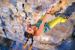 Girl climber climbs on rock. Royalty Free Stock Images