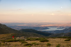 Girl climber contemplates a amazing sunset and moonrise. Girl climber contemplates from the top of the mountain a amazing sunset and the moonrise. Navacerrada Royalty Free Stock Image