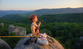 Girl climber on mountain peak on high altitude in evening. Young athletic girl climber sitting secured with rope and meditating with crossed legs on high Stock Photos