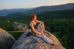 Girl climber on mountain peak on high altitude in evening. Young female rock climber sitting secured with rope on big rock at mountain peak with bare foot Royalty Free Stock Image