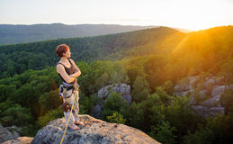 Girl climber on mountain peak on high altitude in evening. Young female climber standing on mountain peak with bare foot enjoying the view on beautiful valley Stock Images