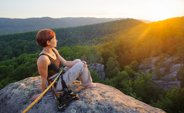 Girl climber on mountain peak on high altitude in evening. Young girl climber sitting secured with rope on big rock at mountain peak with bare foot enjoying the Royalty Free Stock Photos
