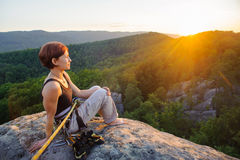 Girl climber on mountain peak on high altitude in evening. Young woman climber sitting secured with rope on big rock at mountain peak with bare foot enjoying the Royalty Free Stock Photography