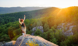 Girl climber on mountain peak on high altitude in evening. Young woman climber standing on mountain peak with raised arms and celebrating her success, looking to Royalty Free Stock Photography