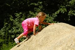 Girl climbing. A girl climbs – and reaches the top of – a gravel pile Royalty Free Stock Images