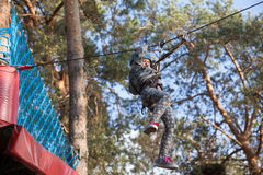Girl climbing in adventure park , rope park Stock Photography