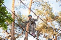 Girl climbing in adventure park , rope park Stock Photos