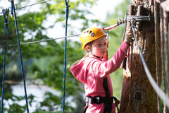Girl climbing in adventure park Stock Images