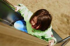 Girl climbing chute. Girl climbing at a chute Royalty Free Stock Image
