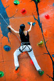 Girl climbing on a climbing wall Royalty Free Stock Photos
