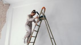Girl climbing down a ladder while holding a paint roller. Girl climbing down a ladder with paint roller in hand stock video footage