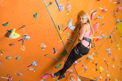 Girl with climbing equipment hanging on a rope Stock Images