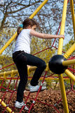Girl climbing a frame in a playground Stock Photo