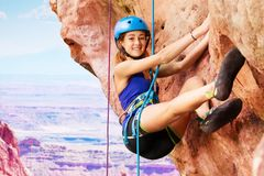 Girl climbing with harness high in the mountains. Smiling young woman rock climbing with harness outdoors high in the mountains Royalty Free Stock Photography