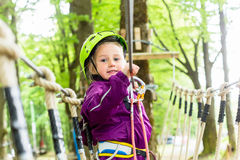 Girl climbing in high rope course Royalty Free Stock Photography