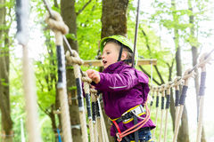 Girl climbing in high rope course Royalty Free Stock Image