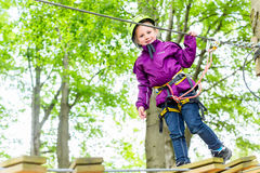 Girl climbing in high rope course Royalty Free Stock Photo