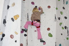 Girl is climbing on indoor wall Stock Photography