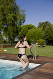 Girl climbing the ladder out of a pool Royalty Free Stock Photography
