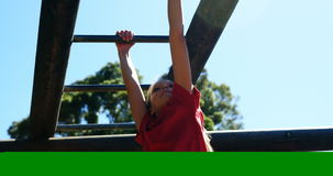 Girl climbing on monkey bar in the boot camp
