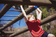 Girl climbing monkey bars during obstacle course training Stock Images