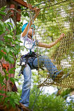 Girl is climbing on net of obstacle course Royalty Free Stock Photography
