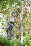 Girl is climbing on net of obstacle course Stock Photography