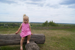 The girl climbing off the log Stock Images