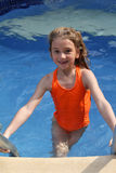 Girl climbing out of pool. Young girl climbs out of pool after swimming Royalty Free Stock Photography