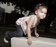 Girl climbing on a park bench Royalty Free Stock Photos
