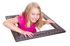 Girl climbing through a picture frame Royalty Free Stock Images