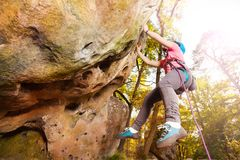 Girl climbing on a rock against autumn forest stock photography