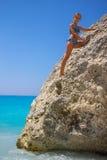 Girl climbing on the rock on the beach Stock Photos