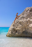 Girl climbing on the rock on the beach Stock Photography