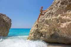 Girl climbing on the rock on the beach Stock Photo