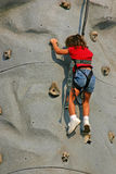 Girl Climbing Rock, Close-Up. Close-up image of young girl climbing rock on sunny day Stock Photos