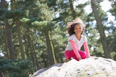 Girl Climbing On Rock In Countryside Stock Image